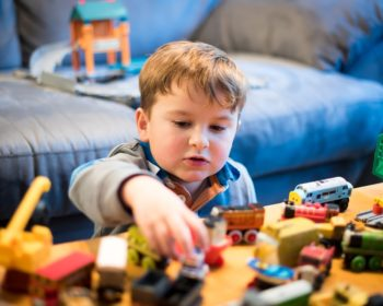 Child playing with Thomas and Friend trainset photo